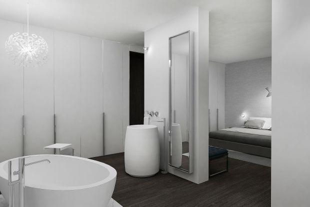 Łazienka coraz częściej pełni rolę domowego salonu kąpielowego i jest łączona we wspólną strefę wypoczynku z sypialnią właścicieli. Taki zabieg zastosowano w projekcie domu w Piasecznie, w którym dominuje elegancki minimalizm.