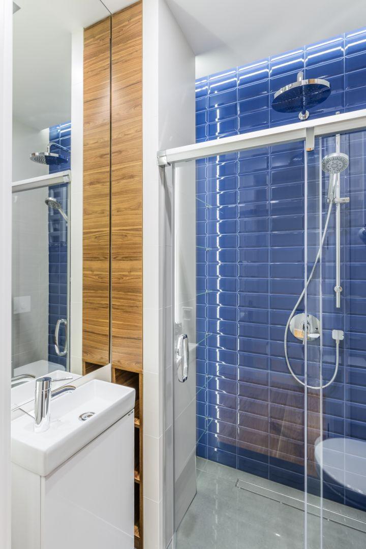 Wzrok przyciąga ściana w strefie prysznica. Zdobią ją płytki z fazowanymi krawędziami, o  intensywnym kobaltowym kolorze. Proj. Monika Pniewska. Fot. Pion Poziom