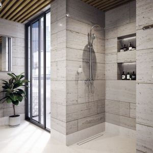 Deszczownia z natryskiem i baterią Algeo znakomicie wygląda w minimalistycznej łazience z otwartą strefą prysznica i odpływem liniowym dyskretnie wkomponowanym w podłogę. Fot. Ferro