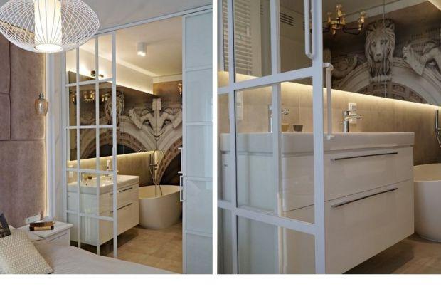 """Efektowna klasycyzująca tapeta, elegancka wolnostojąca wanna oraz oryginalna """"ścianka"""" działowa to cechy charakterystyczne tej łazienki urządzonej przy sypialni."""