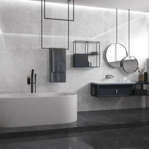 Łazienka z wanną urządzona w nowoczesnym stylu: duet białej wanny w towarzystwie szarych wielkoformatowych płytek z kolekcji Concrete grey i Concrete anthracite. Fot. Cerrad
