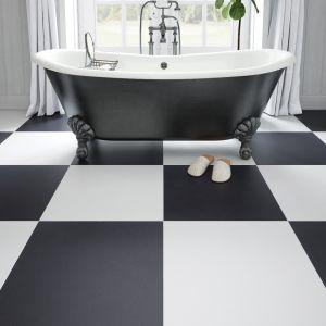 Ozdobna, stojąca w centralnym punkcie wanna wsparta na dekoracyjnych nóżkach, doskonale zagra w połączeniu z matową podłogą w biało-czarną szachownicę z kolekcji Cambia. Fot. Cerrad