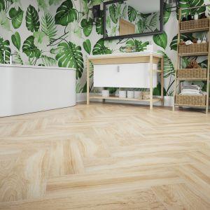 Płytki gresowe jak drewno można układać jak prawdziwą deskę drewnianą - w klasyczną jodełkę. Tak właśnie zrobiono w tej urokliwej aranżacji łazienki z wanną z roślinnymi motywami na ścianie i płytkami z kolekcji Mustiq na podłodze. Fot. Cerrad