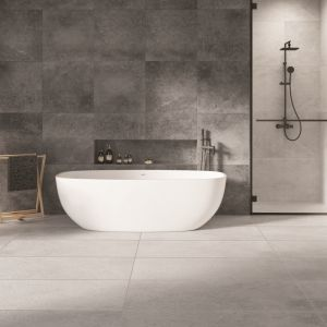 Nowoczesna aranżacja łazienki z wanną wolnostojącą i kabiną prysznicową a w tle szare płytki w surowym wykończeniu z kolekcji Tacoma grey. Na podłodze płytki gresowe Tacoma white. Fot. Cerrad
