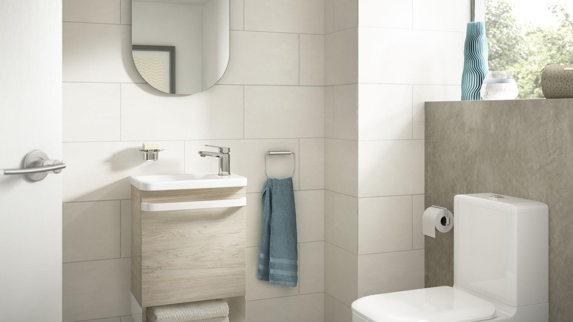 Szafka pod umywalkę Guest z kolekcji Tonic II marki Ideal Standard z dolną metalową półką na ręczniki i uchwytem/wieszakiem w formie długiego relingu. Fot. Ideal Standard