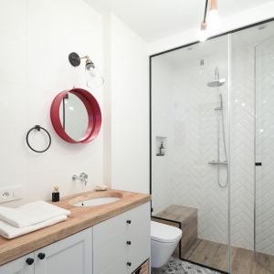 Aranżacja łazienki z błyszczącymi płytkami ceramicznymi o formacie cegiełki ułożonymi w jodełkę na ścianie. Proj. Anna Krzak. Fot. Bartosz Jarosz