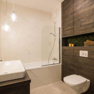Sposób na małą łazienkę: wanna z parawanem, pojemne schowki. Proj. Pracownia KODO