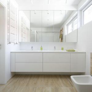 Sposób na małą łazienkę: lustrzane szafki i jasne kolory. Proj. Joanna Ochota. Fot. Bartosz Jarosz