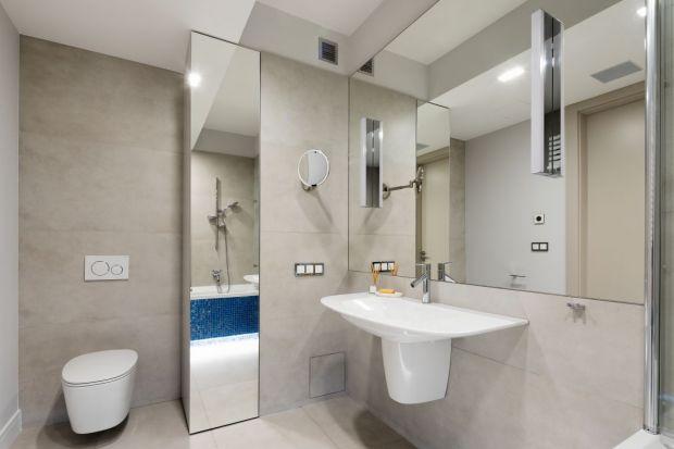 Szarą łazienkę przy sypialni urządzono w szarościach, a kropla błękitu kojarzy się - zgodnie z życzeniem inwestorki - z morskimi klimatami.