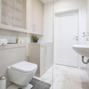 Schowki w łazience: szafki z dekoracyjnymi listwami na frontach wraz z imitującymi marmur płytkami na ścianach nadają łazience klasyczny charakter. W jednym ze schowków ukryto zbyt wyeksponowane grzejniki. Nie widać ich, ale ogrzewają pomieszczenie, bo w płycinie drzwiczek jest siatka, która nie zatrzymuje przepływu ciepła. Proj. Małgorzata Górska-Niwińska, Pracownia Architektoniczna MGN.