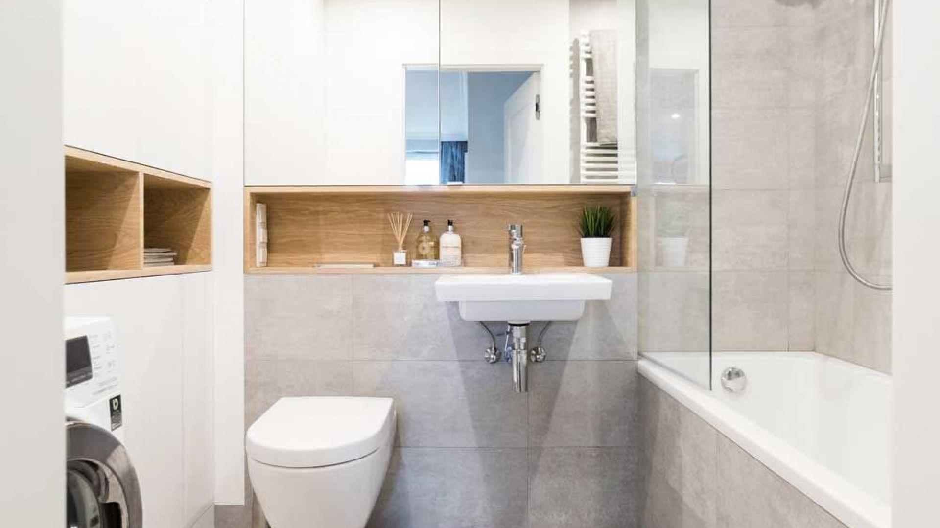 Schowki w łazience: Nad umywalką wysoka szafka z lustrzanymi drzwiczkami, a przy ścianie obok niezwykle pojemna zabudowa od podłogi do sufitu. Ponieważ w pomieszczeniu nie zmieściłaby się szafa o głębokości 70 cm, zdecydowano się na płytszą. Nie udało się więc ukryć pralki. Nie szkodzi, łazienka i tak wygląda bardzo estetycznie. Proj. Małgorzata Górska-Niwińska, Pracownia Architektoniczna MGN.