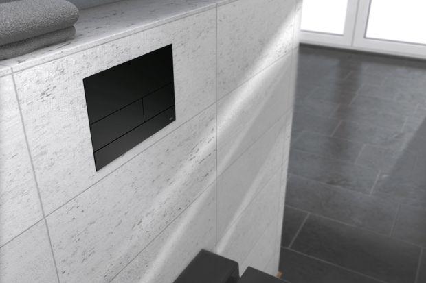 Mat szturmem wkroczył do aranżacji wnętrz, również łazienek. Jednym ze sposobów na jego wprowadzenie do wystroju pomieszczenia jest detal w postaci przycisku spłukującego.