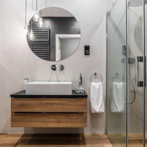 Szara łazienka ocieplona drewnem. Proj. Studio Projekt. Fot. Materiały prasowe Dekorian