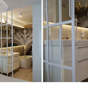 Łazienka przy sypialni oddzielona od niej przezroczystymi przesuwnymi drzwiczkami ze szprosami na szkle. Proj. Barbara Godawska, iHome Studio.