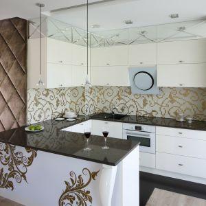 Meble w kolorze złamanej bieli stanowią spokojne tło dla bogato zdobionych elementów. Złote ornamenty przewijają się przez całą aranżację. Zdobią zarówno stylowy półwysep, jak i białą mozaikę nad blatem roboczym. Projekt Agnieszka Hajdas-Obajtek. Fot. Bartosz Jarosz.