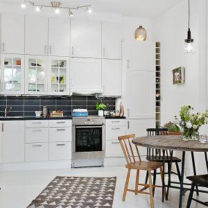Salon, jadalnia i kuchnia stanowią jeden przestronny pokój dzienny, który stylistycznie spaja wszechobecna biel. Fot. Alvhem Makleri.