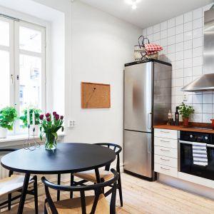 Prosta i bezpretensjonalna kuchnia w białym kolorze została zintegrowana z niewielką jadalnią. Fot. Stadshem.