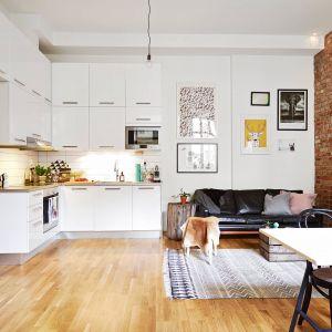 W niewielkim mieszkaniu pokój dzienny połączony z aneksem kuchennym w białym kolorze. Fot. Stadshem.