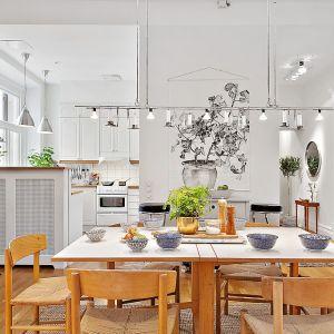 Inspirowane skandynawskim stylem wnętrze przyciąga elegancką prostotą. Przestronną jadalnię od kuchni oddziela stylowy barek. Fot. Alvhem Makleri.