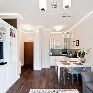 Niewielkie wnętrze urządzono w typowo skandynawskim stylu. Dzięki aranżacji w stylu open space, poszczególne funkcje przestrzeni mieszkania przenikają się, tworząc komfortową całość. Fot. Sun & Snow.