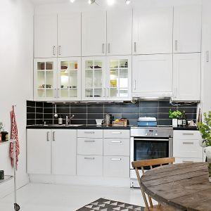 W niewielkim wnętrzu zabudowę kuchenną umiejscowiono tylko na jednej ścianie. Charakteru wykończonej na biało kuchni dodają kontrastujące czarne kafle, które zdobią ścianę nad blatem. Fot. Alvhem Makleri.