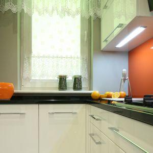 Mimo że kolor pomarańczowy – pod postacią szkła na ścianie – to tylko akcent, skutecznie ociepla i zdobi wnętrze. Odpowiada też za pogodny i pełen energii charakter kuchni. Fot. Bartosz Jarosz.