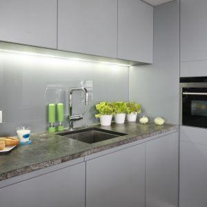 W szarej kuchni poza światłem górnym zdecydowano się na taśmy led montowane pod szafkami. Projekt: Monika i Adam Bronikowscy. Fot. Bartosz Jarosz.