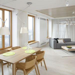 W nowoczesnym wnętrzu nad stołem zamontowano lampy wyglądem nawiązujące do przemysłowych reflektorów. Projekt Maciej Brzostek. Fot. Bartosz Jarosz.
