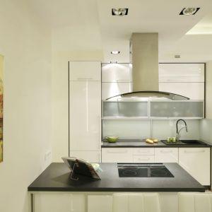 W jasnej i przytulnej kuchni dominuje biel w swej czystej odsłonie - w postaci mebli, oraz nieco złamanej wersji - na ścianach. Projekt Marta Kilan. Fot. Bartosz Jarosz.