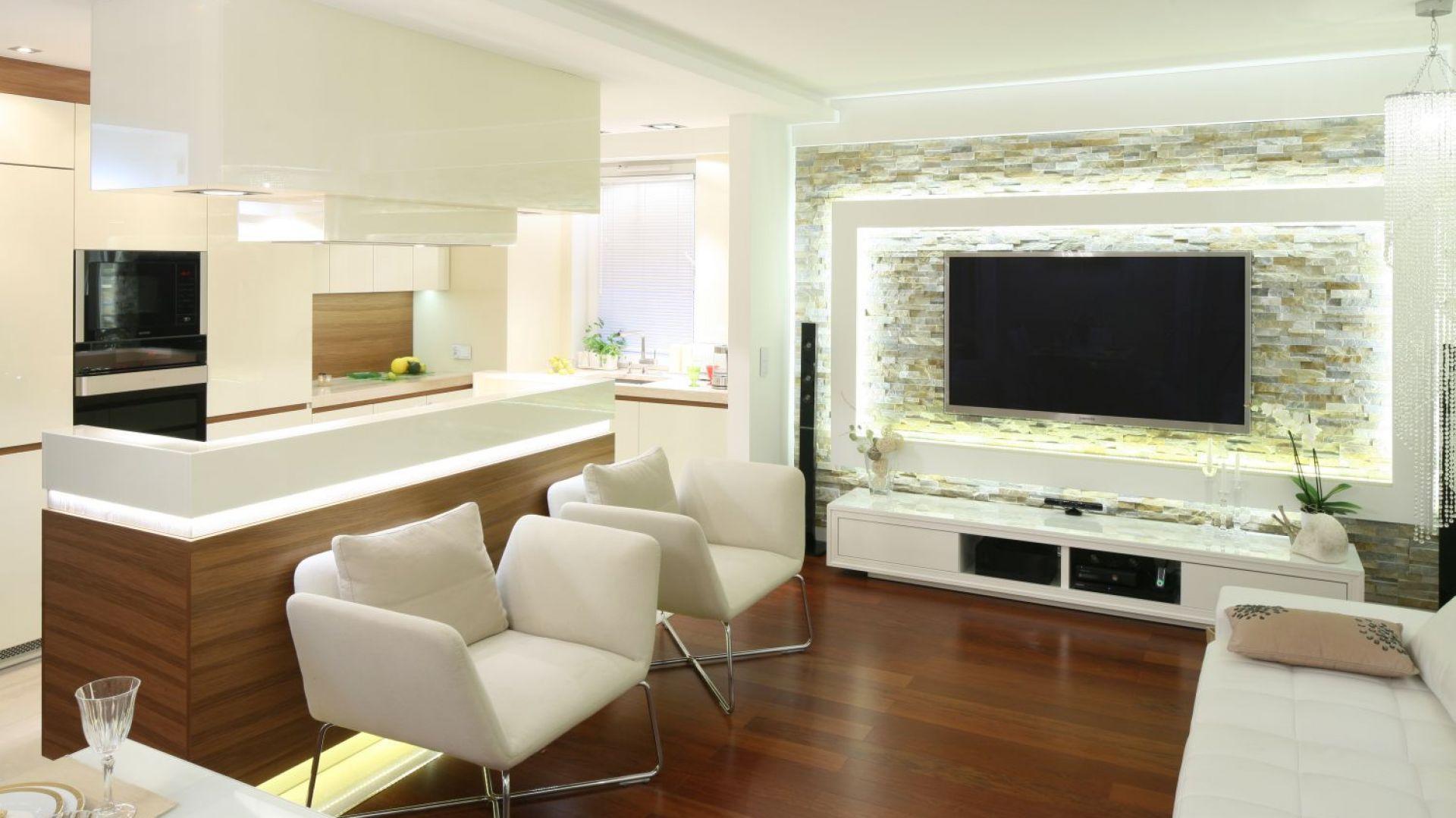 W niewielkim mieszkaniu kuchnię umiejscowiono wzdłuż salonu, od którego oddziela ją tylko wyspa. Biel i drewno, obecne w obu strefach, nawzajem się przenikają prowadząc subtelną grę znaczeń poszczególnych ról użytkowych. Projekt Małgorzata Mazur. Fot. Bartosz Jarosz.