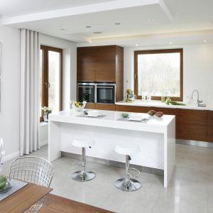 Kuchnia w bieli i drewnie to kontynuacja eleganckiego salonu. Przy wyspie nie tylko przygotowuje się posiłki, ale także zasiada do wspólnych pogawędek przy kawie. Proj. Piotr Stanisz. Fot. Bartosz Jarosz.