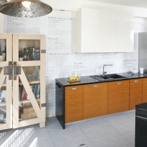 Designerska witryna z drewna dębowego  pełni  funkcję przechowywania,  jak również  podkreśla loftowy charakter aranżacji. Projekt Marta Kruk. Fot. Bartosz Jarosz.