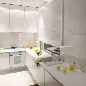 W białej kuchni ściany wyłożono tapetą w tym samym kolorze. W miejscach newralgicznych zabezpiecza ją transparentne szkło. Projekt Katarzyna Merta-Korzniakow.Fot. Bartosz Jarosz.