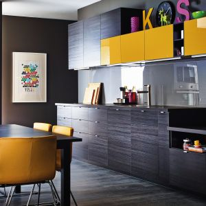 Na zdjęciu: kuchnia Metod firmy IKEA; ściana wykończona przezroczystym szkłem podkreśla ciekawą kolorystykę mebli – imitującą czarne drewno oraz żółty w połysku. Fot. IKEA.