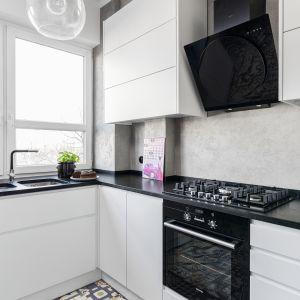 Białe meble mają proste kształty. Górne szafki wyposażone w otwieranie dotykowe, zaś dolne – w eleganckie, krawędziowe uchwyty. Proj. Marta Kramkowska. Fot. Bartosz Jarosz.