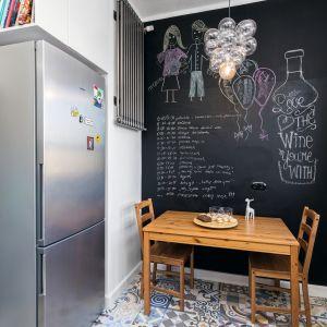 Nad lodówką wykonano szafkę na książki. Grzejnik został przeniesiony spod okna na ścianę w jadalni. To model pasujący do stylistyki loft kuchni. Proj. Marta Kramkowska. Fot. Bartosz Jarosz.