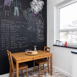 Kuchnia to osobne pomieszczenie. W strefie jadalni całą ścianę pomalowano farbą tablicową. Można na niej rysować i pisać. To oryginalna dekoracja, a zarazem praktyczne rozwiązanie. Proj. Marta Kramkowska. Fot. Bartosz Jarosz.