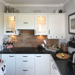 W stylizowanej kuchni nie mogło zabraknąć cegły. Stała się ona ozdobą ściany między szafkami kuchennymi. Projekt Magdalena Kwiatkowska. Fot. Bartosz Jarosz.