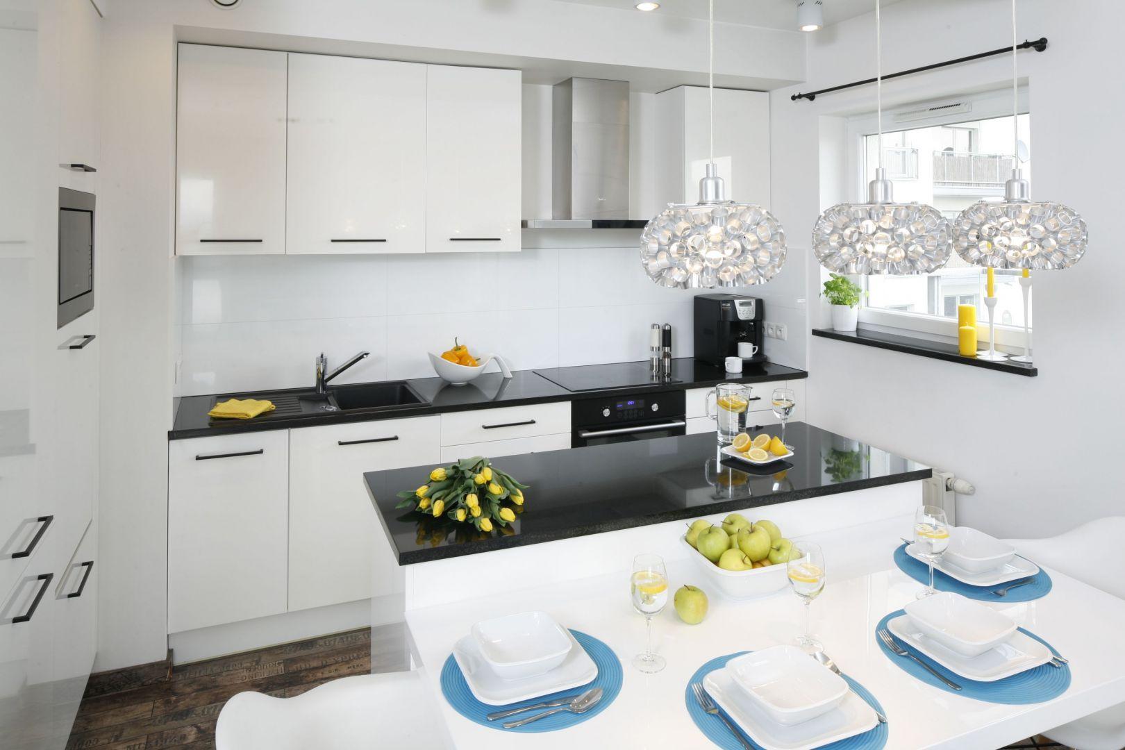 W niedużym mieszkaniu kuchnię urządzono w bieli. Ożywia ją czerń oraz dodatki w intensywnych żółtych i turkusowych kolorach. Projekt Katarzyna Uszok. Fot. Bartosz Jarosz.