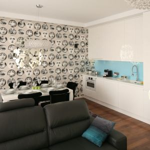 Mała kuchnia znajduje się w apartamencie weekendowym. To aneks wyposażony w proste, białe meble. Tuż obok usytuowano jadalnię. Projekt Anna Maria Sokołowska. Fot. Bartosz Jarosz.