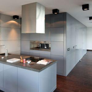 W zamkniętej w kubiku kuchni dominują szarości. Jasne na ścianach imitujących beton, ciemne w kolorze wysokiej zabudowy oraz półwyspu kuchennego. Projekt Justyna Smolec. Fot. Bartosz Jarosz.