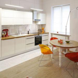 W otwartej na salon kuchni zdecydowano się na zabudowę kuchenną na jedną ścianę.  Szafki górne w białym kolorze nie tylko zapewniają sporo miejsca do przechowywania, ale też optycznie powiększają przestrzeń. Projekt: Agnieszka Żyła. Fot. Bartosz Jarosz.