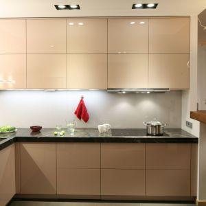 W przestronnej kuchni główną ozdobą kuchni jest biżuteryjny onyks, który zdobi jedną ze ścian. Na drugiej ze ścian zamontowano dwa rzędy szafek w eleganckim kolorze. Projekt Kuba Kasprzak, Paweł Pałkus. Fot. Bartosz Jarosz.