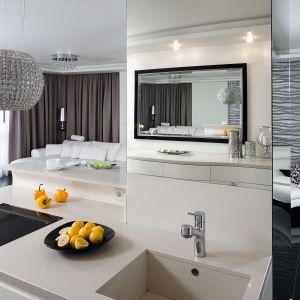Lustro w dekoracyjnej ramie to ozdobny element wnętrza. Jego zadaniem jest także ukrycie części kuchennej. Dzięki temu wnętrze nie wyróżnia się na tle salonu.