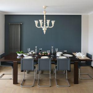 Dużą, elegancka jadalnię urządzono w specjalnej wnęce. Jej nowoczesny charakter podkreśla ściana pomalowana na stonowany granat, do której dobrano kolor krzeseł. Projekt Izabella Kolor. Fot. Bartosz Jarosz.