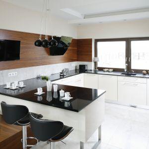 W eleganckiej kuchni telewizor zamontowano tuż nad półwyspem z barem - między kuchnią a jadalnią. Projekt: Piotr Stanisz. Fot. Bartosz Jarosz.