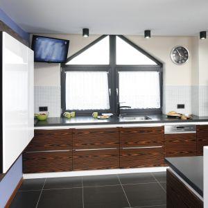 W przestronnej kuchni zdecydowano się na zabudowę w kształcie litery U. Duża ilość szafek oraz okno prawie na całą ścianę pozwoliły zamontować tu telewizor. Projekt: Marta Kilan. Fot. Bartosz Jarosz.