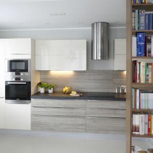 Niewielką kuchnię urządzono w bieli i drewnie. Od salonu oddziela ją praktyczny regał na książki. Projekt Joanna Morkowska-Saj. Fot. Bartosz Jarosz.