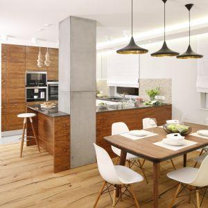 W  otwartej przestrzeni wyraźnie wyodrębniono salon, kuchnię i jadalnię, nie zatracając przy tym tak ważnej spójności stylistycznej. Udało się ją zachować dzięki konsekwentnemu zastosowaniu tych samych materiałów wykończeniowych w całym mieszkaniu. Projekt Agnieszka Hajdas-Obajtek. Fot. Bartosz Jarosz.