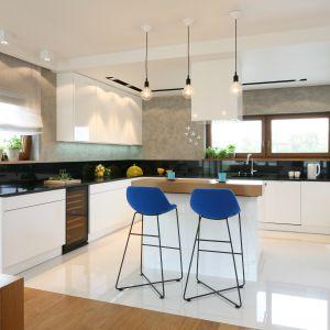 W dużej i przestronnej kuchni białe meble lakierowane na wysoki połysk dumnie prezentują się na tle szarych ścian pomalowanych farbą imitującą strukturę betonu. Projekt Małgorzata Galewska. Fot. Bartosz Jarosz.
